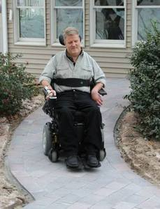 Homeowner Rob Butts tries out his new heated wheelchair ramp, made possible by A Concord Carpenter, WarmlyYours, and a team of contractors volunteering their time and expertise.