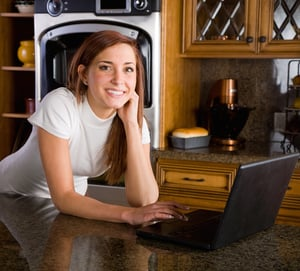 Woman enjoying a warm countertop as she works on her laptop