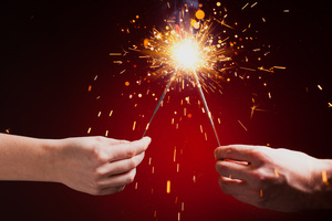 Hands holding sparklers together