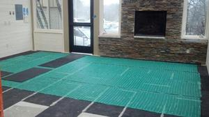 Installing CeraZorb synthetic cork underlayment under the TempZone floor heating system prevents heat loss through the concrete below, allowing more heat to radiate into the room.